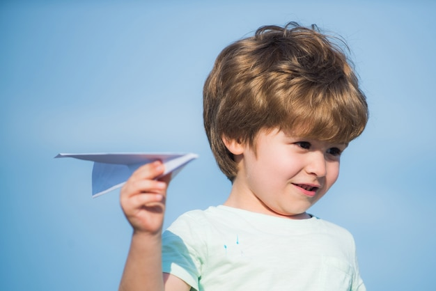 Glückliches kind süßer junge mit papier aipplene glückliches kind auf sommerfeld traum vom fliegenden konzept familientr ...