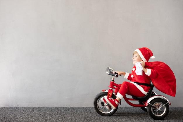 Glückliches kind trägt weihnachtskostüm kind reitet fahrrad