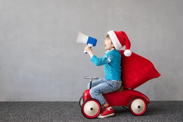 Glückliches kind trägt weihnachtskostüm kind reitet spielzeugauto lustiges kind schreit durch lautsprecher