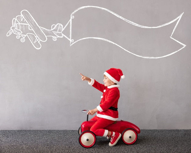 Glückliches kind trägt weihnachtskostüm kind reitet spielzeugauto weihnachtsfeiertagskonzept