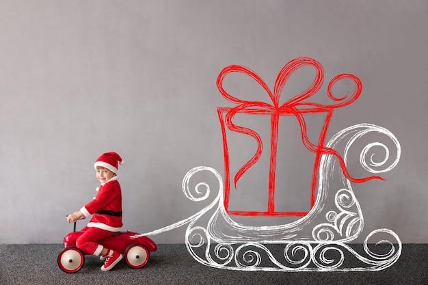 Glückliches kind trägt weihnachtskostüm kind reitet spielzeugauto