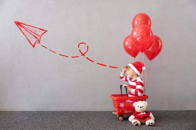 Glückliches kind trägt weihnachtskostüm kind sitzt im einkaufswagen mit roten luftballons