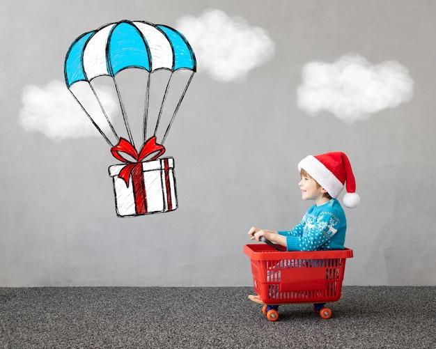 Glückliches kind trägt weihnachtskostüm kind sitzt im einkaufswagen