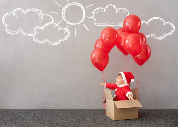 Glückliches kind trägt weihnachtskostüm kind sitzt in box mit roten luftballons