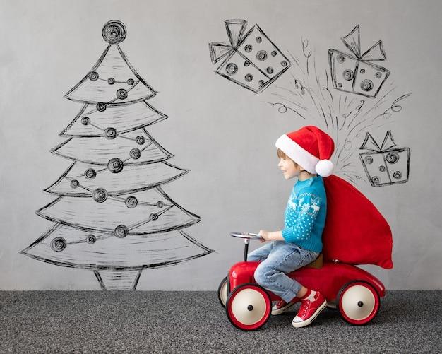 Glückliches kind trägt weihnachtspullover kind reitet spielzeugauto lustiges spielendes kind
