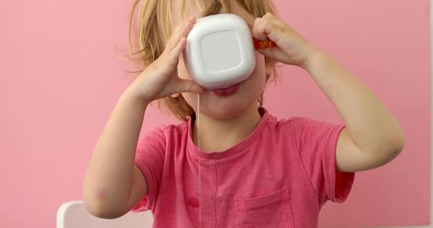 Glückliches kind trinkt milch von einer schale auf rosa