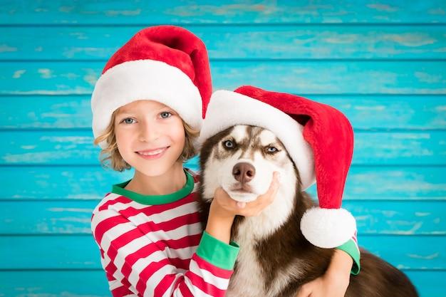 Glückliches kind und hund an heiligabend kind und haustier gekleidet in weihnachtsmann-hut baby spaß mit h