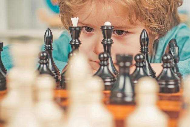 Glückliches kind und kindheit kleiner kluger junge, der an schach denkt süßer kleiner junge, der schach spieltches