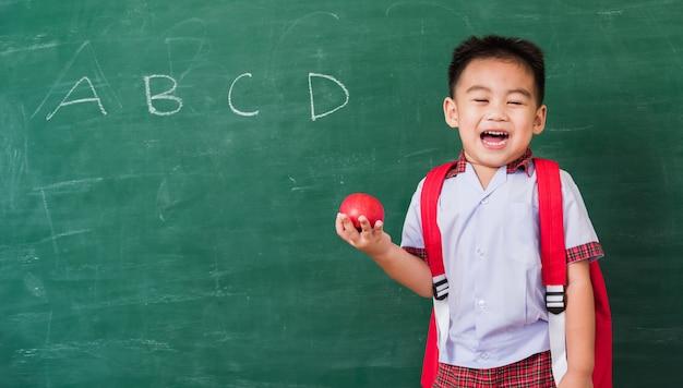 Glückliches kind vom kindergarten in der studentenuniform mit schultasche halten roten apfel auf hand