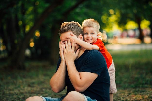 Glückliches kind, welches die augen seines vaters bedeckt