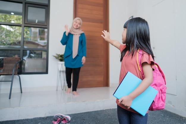 Glückliches kind winkt mutter auf wiedersehen, bevor es morgens zur schule geht