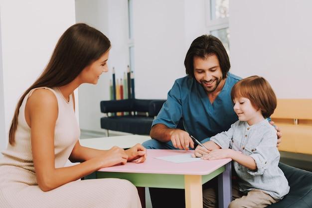 Glückliches kind zeichnet bei doctor office pediatric clinic.