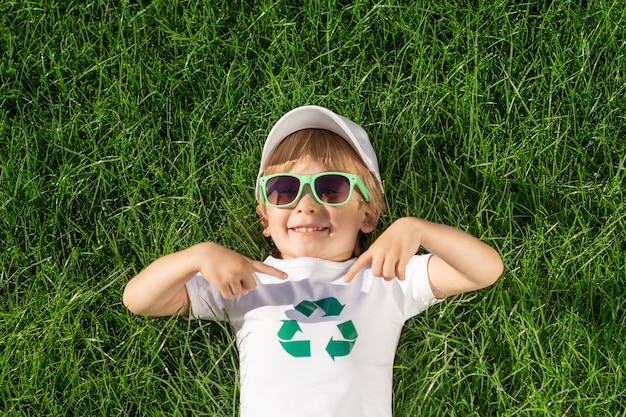 Glückliches kind zeigt finger auf recycling-zeichen auf t-shirt