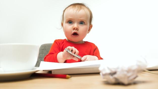 Glückliches kindbaby, das mit tastatur des modernen computers oder des laptops im weißen studio sitzt