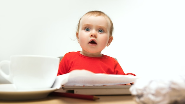 Glückliches kindbaby, das mit tastatur des modernen computers oder des laptops im weißen studio sitzt.