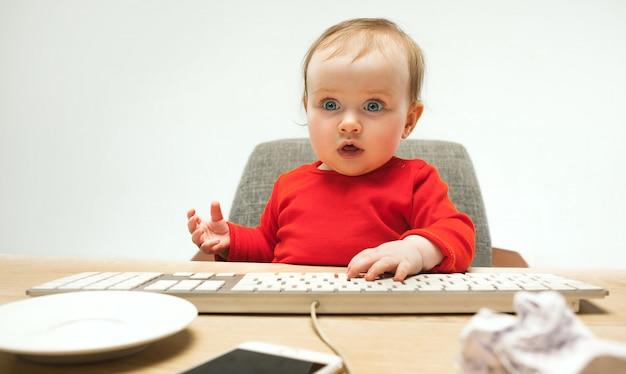 Glückliches kindbaby, das mit tastatur des modernen computers oder des laptops lokalisiert auf einem weißen studio sitzt