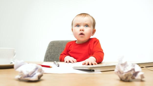 Glückliches kindbaby, das mit tastatur des modernen computers oder des laptops lokalisiert auf einem weißen studio sitzt.