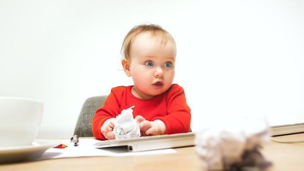 Glückliches kindbaby, das mit tastatur des modernen computers oder des laptops lokalisiert auf weiß sitzt