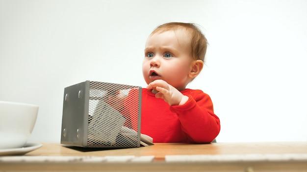 Glückliches kindbaby-kleinkind, das mit tastatur des computers lokalisiert auf einem weißen hintergrund sitzt