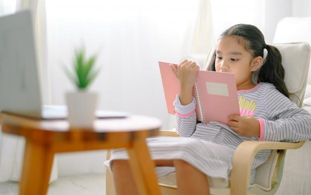 Glückliches kinderkleines asiatisches mädchen, das zu hause bücher auf dem tisch im wohnzimmer, familientätigkeitskonzept liest