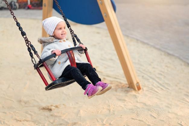 Glückliches kindermädchen auf schwingen im sonnenuntergangfall. kleinkind, das im herbst auf dem naturpark spielt
