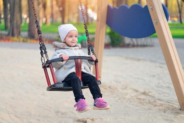 Glückliches kindermädchen auf schwingen im sonnenuntergangfall