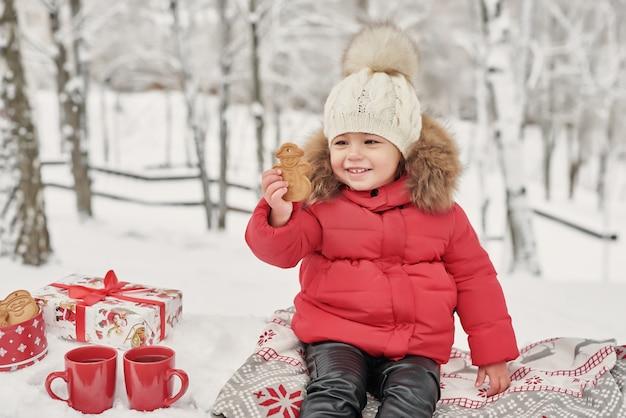 Glückliches kindermädchen auf winterweg tee draußen trinkend. lächelndes baby kleines kind, das in den winterweihnachtsfeiertagen spielt. weihnachtsfamilie im winterpark. mädchen im winterwald.