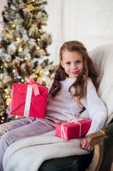 Glückliches kindermädchen, das auf sessel sitzt, bedeckt mit einer decke