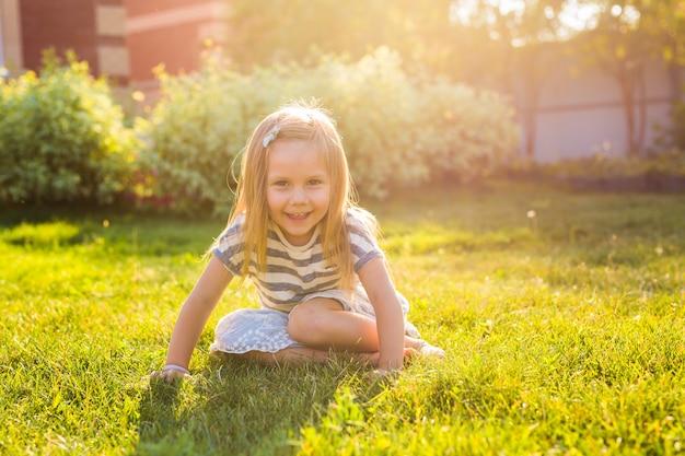 Glückliches kindermädchen, das auf wiese im sommer in der natur spielt
