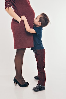 Glückliches kindermädchen, das den bauch, die schwangerschaft und das neue lebenkonzept der schwangeren mutter umarmt