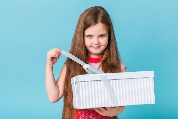 Glückliches kindermädchen, das geschenkbox auf blauem hintergrund öffnet. weihnachtszeit. kindergeburtstag.