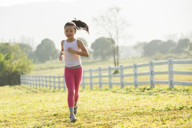 Glückliches kindermädchen, das im sommer in der natur auf der wiese läuft. warmes sonnenlicht flackern. asiatische wenig läuft in einem park. outdoor-sport und fitness, bewegung und wettkampflernen für die entwicklung von kindern. Kostenlose Fotos
