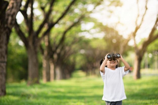 Glückliches kindermädchen, das mit fernglas spielt