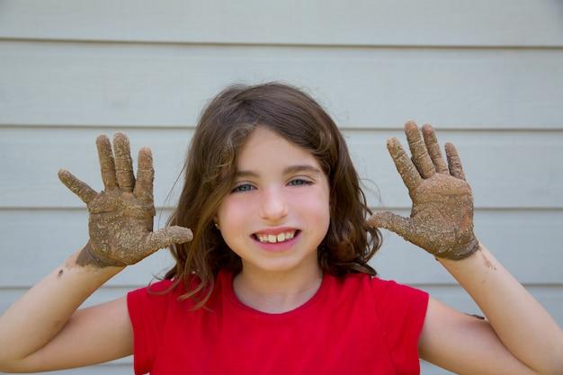 Glückliches kindermädchen, das mit schlamm mit dem schmutzigen handlächeln spielt