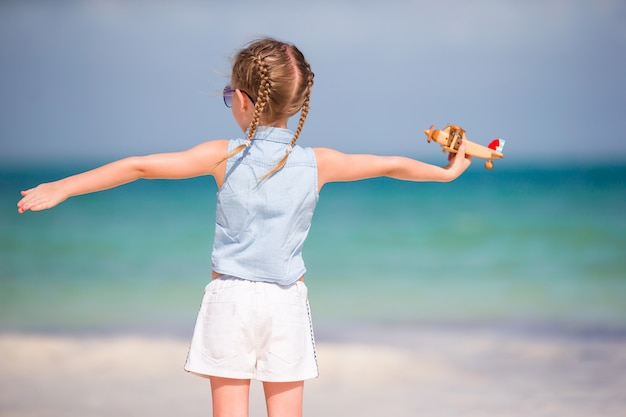 Glückliches kindermädchen, das mit spielzeugflugzeug auf dem strand spielt. kindertraum, pilot zu werden