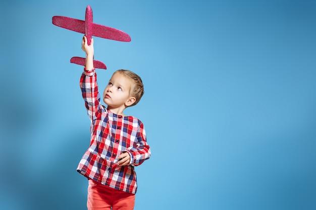Glückliches kindermädchen, das mit spielzeugflugzeug spielt. der traum, pilot zu werden.