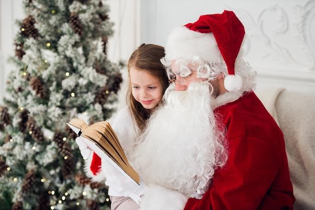 Glückliches kindermädchen, das santa umarmt und lacht