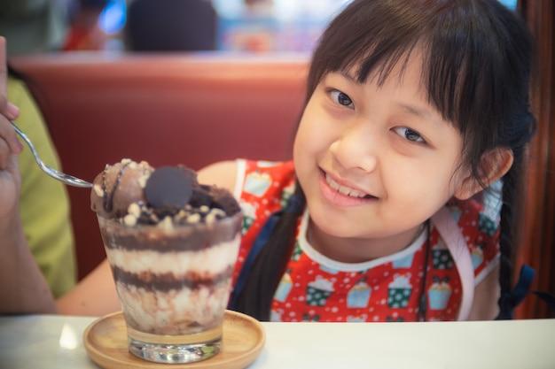 Glückliches kindermädchen, das schokoladeneis mit lächeln isst