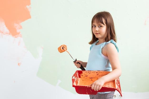 Glückliches kindermädchen malt die wand mit orange farbe