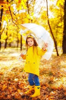 Glückliches kindermädchen mit einem regenschirm und gummistiefeln ein herbstweg