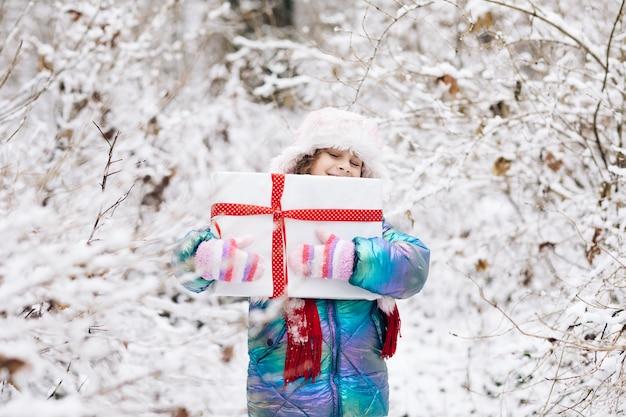 Glückliches kindermädchen mit weihnachtsgeschenk auf einem winterspaziergang in der natur.