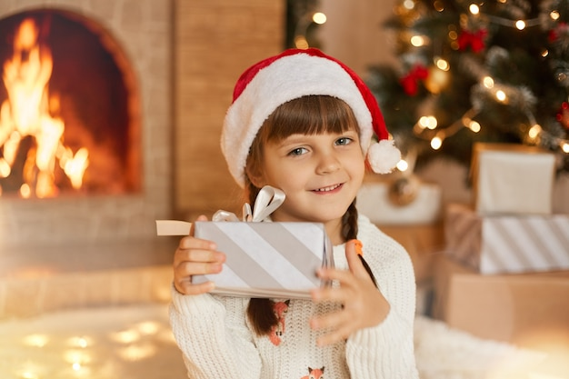 Glückliches kindermädchen mit weihnachtsgeschenk, das direkt in die kamera schaut