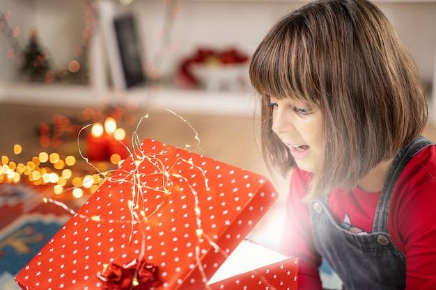 Glückliches kindermädchen mit weihnachtsgeschenk-eröffnungsüberraschung