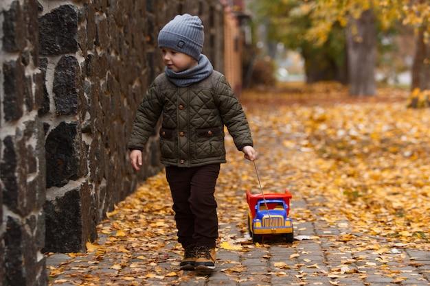 Glückliches kinderporträt mit spielzeugauto auf gelbem herbst. kleiner lächelnder junge, der mit großem spielzeugauto in der herbststadtstraße geht und spaß hat