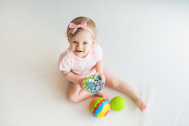Glückliches kinderzimmerbaby, das mit buntem gummiball zu hause spielt