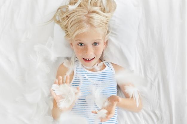 Glückliches kindheitskonzept. freizeit, spaß und entspannung. top bild des entzückenden blonden sommersprossigen kleinen vorschulkindes, das durch fliegende federn nach kissenschlacht in ihrem zimmer schaut