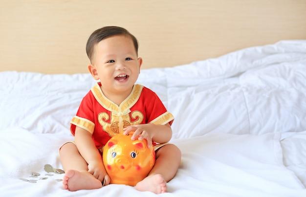 Glückliches kleines asiatisches baby im kleid der traditionellen chinesen mit einem sparschwein auf bett.