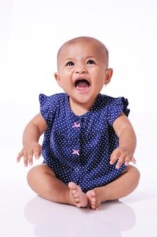 Glückliches kleines asiatisches baby lachend, das auf weißem boden sitzt, lokalisiert über weißer wand