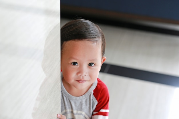 Glückliches kleines asiatisches baby versteckt hinter einem eckzimmer