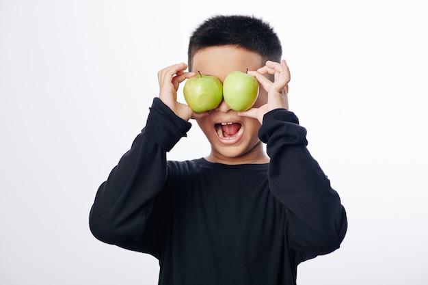 Glückliches kleines asiatisches kind, das grüne äpfel vor augen hält und mund öffnet